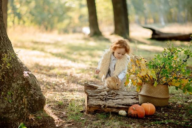 Girl with pet rabbit and pumpkins